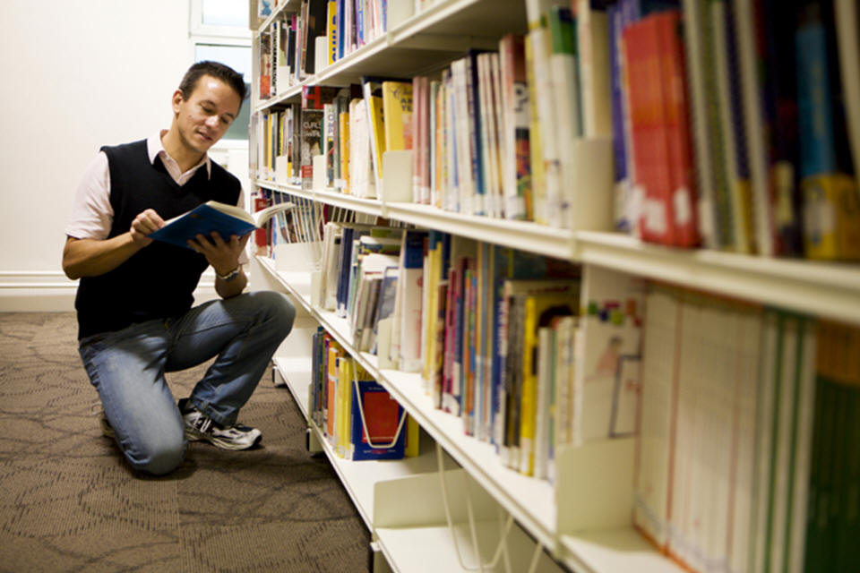 Young Man Reading a Book in a Library Book Shelf