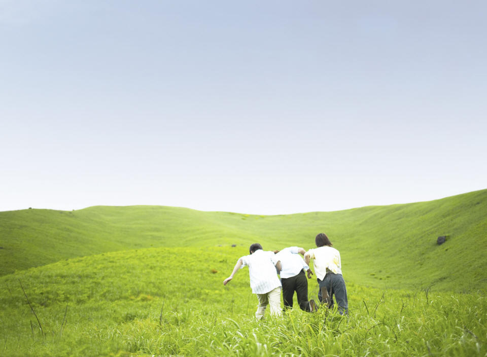 Three People Running through a large field of green grass